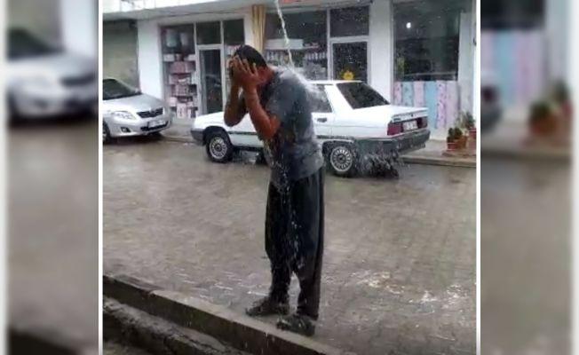 Ağustos'ta yağan yağmur altında banyo yaptı